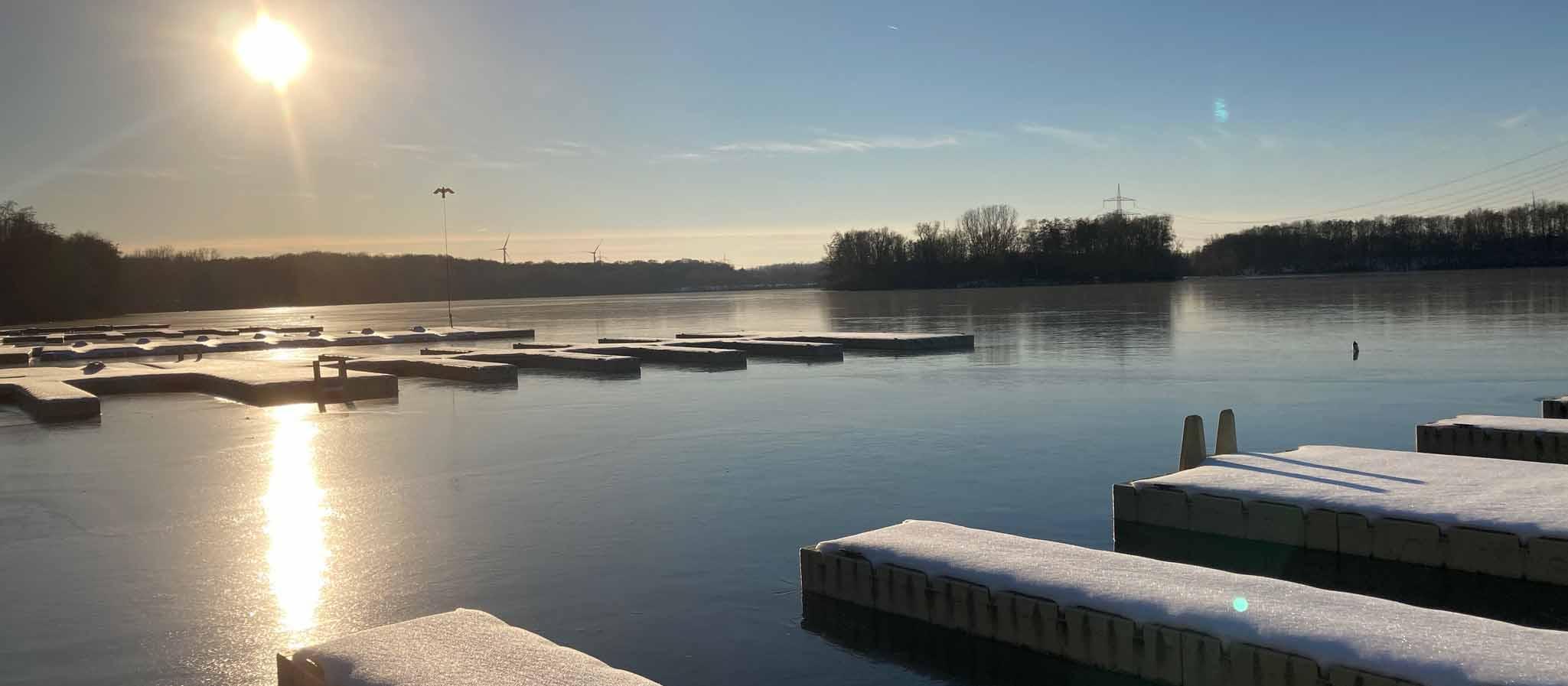 Zugefrorener See im Winter mit Sonne