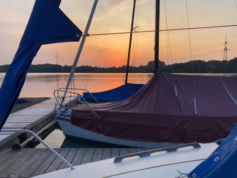 Sonnenuntergang auf Stegen vor Booten